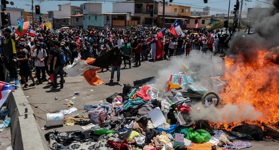 Grupo de personas queman carpas que eran utilizadas por venezolanos para pernoctar en la calle en Iquique, Chile. (EFE/ Johan Berna).