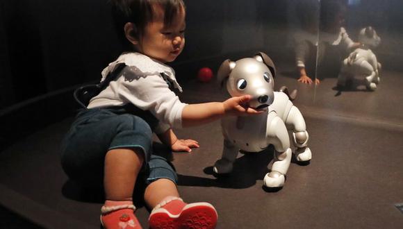 Una pequeña juega con el pequeño perro Aibo de Sony, un robot con inteligencia artificial en la exposición de Londres. (Foto: AFP)