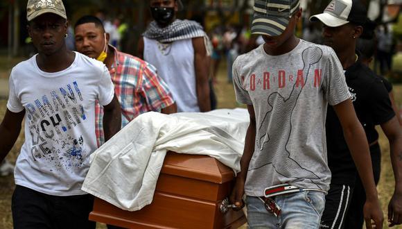 Amigos y familiares llevan el féretro de uno de los cinco jóvenes asesinados en un campo de caña de azúcar en Cali, Colombia, el 13 de agosto de 2020. (Foto: Luis ROBAYO / AFP).