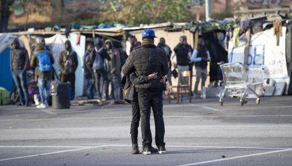 Dos migrantes se abrazan mientras esperan a que autoridades procedan al desmantelamiento del campamento de Baobab, en el que permanecían alrededor de 200 migrantes, en Roma. (Foto referencial: EFE)