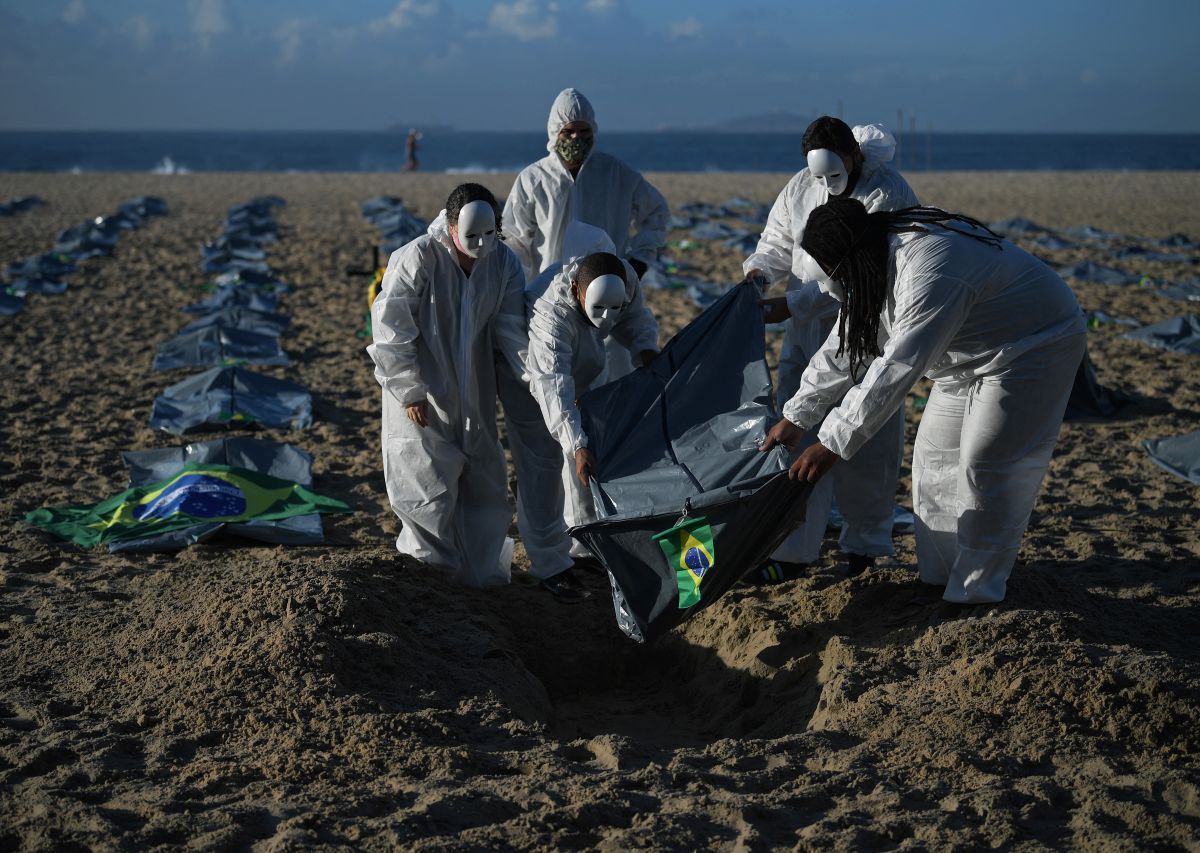 Protesters from the Rio de Paz human rights activist group lower a body bag onto a symbolic grave on Copacabana beach. (Photo by CARL DE SOUZA / AFP).
