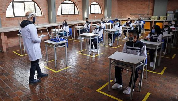 Estudiantes atienden la clase con los pupitres separados y respetando las recomendaciones para evitar el contagio de coronavirus durante el retorno al colegio en Bogotá, Colombia. (EFE/ Mauricio Dueñas Castañeda).