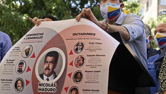 El líder opositor en Venezuela Juan Guaidó muestra el pasado miércoles un cartel que representa al presidente venezolano Nicolás Maduro para expresar sus presuntos vínculos con criminales y dictadores. (Foto: Yuri CORTEZ / AFP)