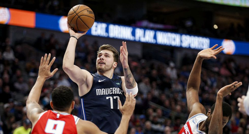 Dallas Mavericks guard Luka Doncic (77) attempts a shot as Sacramento Kings guard Cory Joseph (9) and forward Harrison Barnes (40) defend during the first half of an NBA basketball game, Wednesday, Feb. 12, 2020, in Dallas. (AP Photo/Brandon Wade)