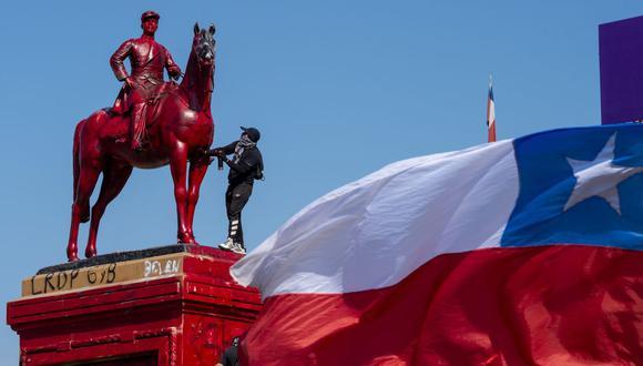 Un manifestante pinta de rojo el monumento del General Baquedano durante una protesta contra el gobierno del presidente de Chile, Sebastián Piñera, en la Plaza Italia. (Foto de MARTIN BERNETTI / AFP).