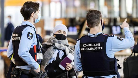 Miembros de la policía militar holandesa (Marechaussee) hablan con un viajero en la nueva sala de salidas del aeropuerto de Rotterdam La Haya en Rotterdam, Países Bajos. (Foto: EFE / EPA / REMKO DE WAAL).