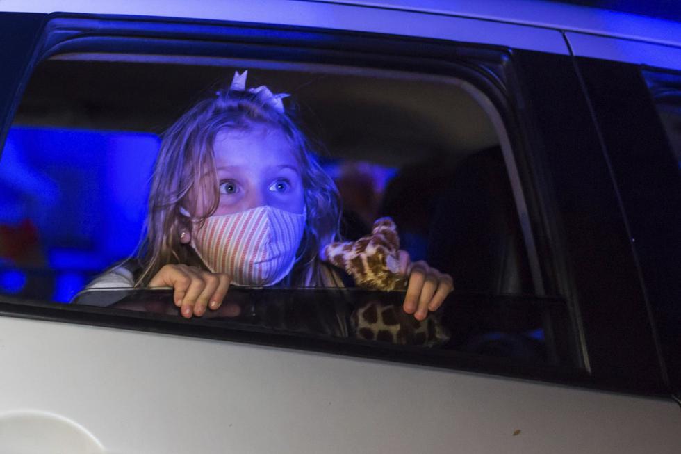 Una niña que usa una máscara protectora observa una actuación desde el interior de un automóvil, en el parque de diversiones temático de terror Hopi Hari, en el suburbio de Vinhedo de Sao Paulo, Brasil. (Foto AP / Carla Carniel).