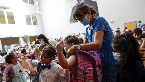 Imagen referencial. Una cuidadora que usa una mascarilla por el coronavirus ayuda a los alumnos con sus mochilas durante una ceremonia en una escuela primaria de Alemania. (EFE/EPA/FELIPE TRUEBA).