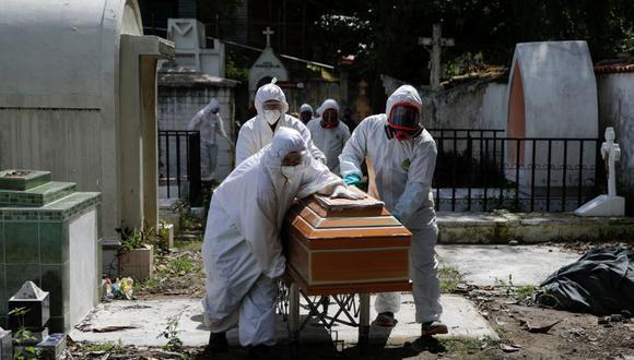 Trabajadores de un cementerio mueven el ataúd de una mujer, que murió de coronavirus (COVID-19), durante su funeral en el cementerio de Santa Tecla, en El Salvador. (Foto: Reuters / José Cabezas)