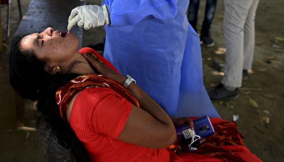 Un trabajador médico toma una muestra de hisopo de una mujer para una prueba de coronavirus en Nueva Delhi, India, el 4 de abril de 2021. (Foto de Sajjad HUSSAIN / AFP).