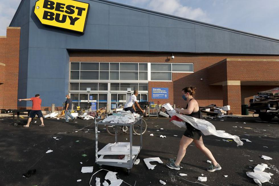 Un grupo de personas ayuda a limpiar el estacionamiento de una tienda Best Buy que fue saqueada en la noche en Chicago, Estados Unidos. (Foto AP / Charles Rex Arbogast).