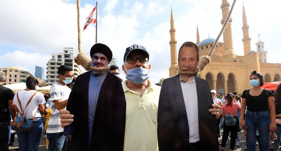 Un hombre posa para una foto con un recorte de cartón de Hassan Nasrallah (izquierda), líder del movimiento musulmán chiita Hezbolá, y el exministro de Relaciones Exteriores Gibran Bassil colgado por manifestantes libaneses en el centro de Beirut. (Foto: AFP).
