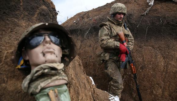 Un militar ucraniano camina en una trinchera junto a una especie de maniquí mientras se encuentra en su puesto en la línea del frente con los separatistas respaldados por Rusia. (Foto: AFP).