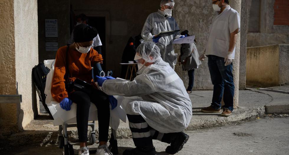 Bomberos franceses de Marins-Pompiers de Marsella con equipos de protección examinan a una mujer de 19 años, sospechosa de estar infectada con el nuevo coronavirus. (AFP/CHRISTOPHE SIMON).