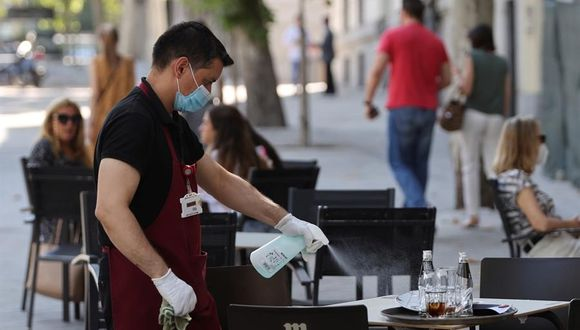 Un camarero desinfecta una mesa tras las marcha de los clientes de la terraza de un bar del centro de Madrid. La Comunidad de Madrid declaró obligatorio el uso de mascarilla en todos los espacios, abiertos o cerrados para frenar el rebrote de coronavirus en España. (EFE/Mariscal).