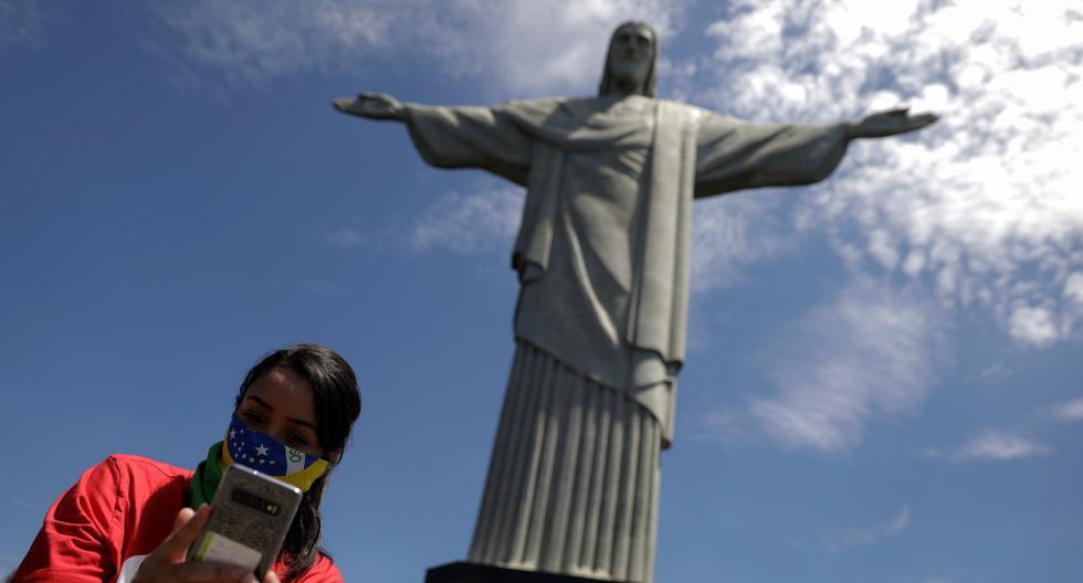 Una mujer se toma una foto ante el Cristo Redentor del Corcovado, en Río de Janeiro, que fue declarado en emergencia por el coronavirus. (REUTERS/Ricardo Moraes).