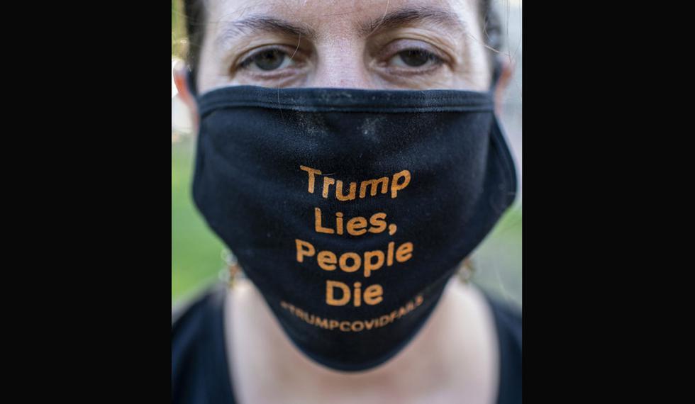 """Un manifestante con una máscara facial que dice """"Trump miente, la gente muere"""" posa mientras muestra bolsas de cadáveres falsas durante una protesta frente a la Casa Blanca en Washington, DC. (Foto: AFP/Eric BARADAT)"""