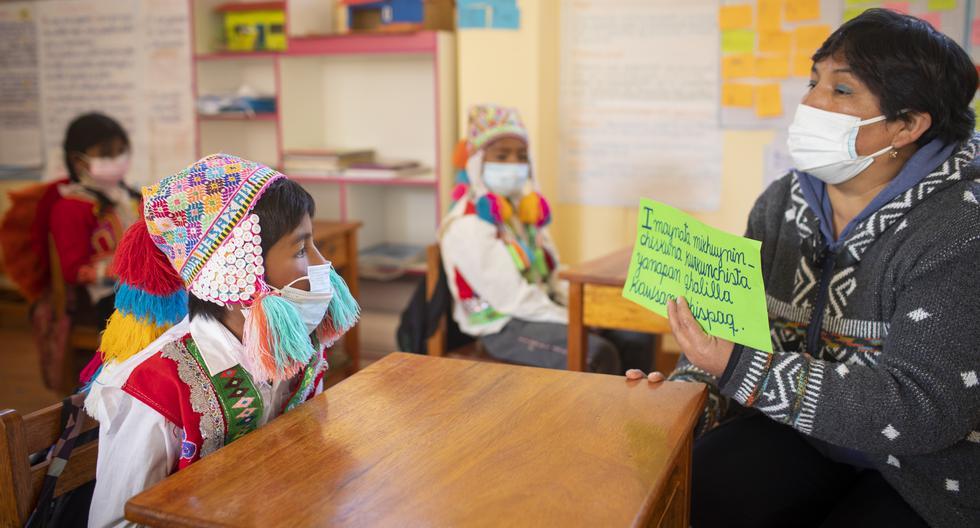 """La maestra de Alto Serranuyoc Rosa María Quispe iba una vez por semana a la escuela para que los niños no se atrasen. Desde agosto –ya vacunada– va a diario. En la foto, enseña sobre la alimentación. """"Cómo nuestros alimentos ayudan a nuestro cuerpo para vivir sanamente"""", se lee en el letrero. (Foto: Richard Hirano / Somos)"""