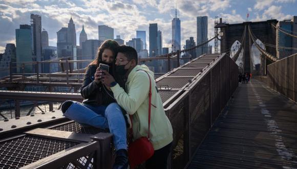 Una pareja mira su teléfono móvil mientras posan para fotos en el puente de Brooklyn antes del horizonte del bajo Manhattan, Nueva York. (Foto: Ed JONES / AFP)