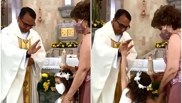 Se volvió viral en Internet el inocente gesto de una niña que le chocó la mano a un cura mientras la bendice durante una misa. (Foto: Un Nuevo Día / Facebook)