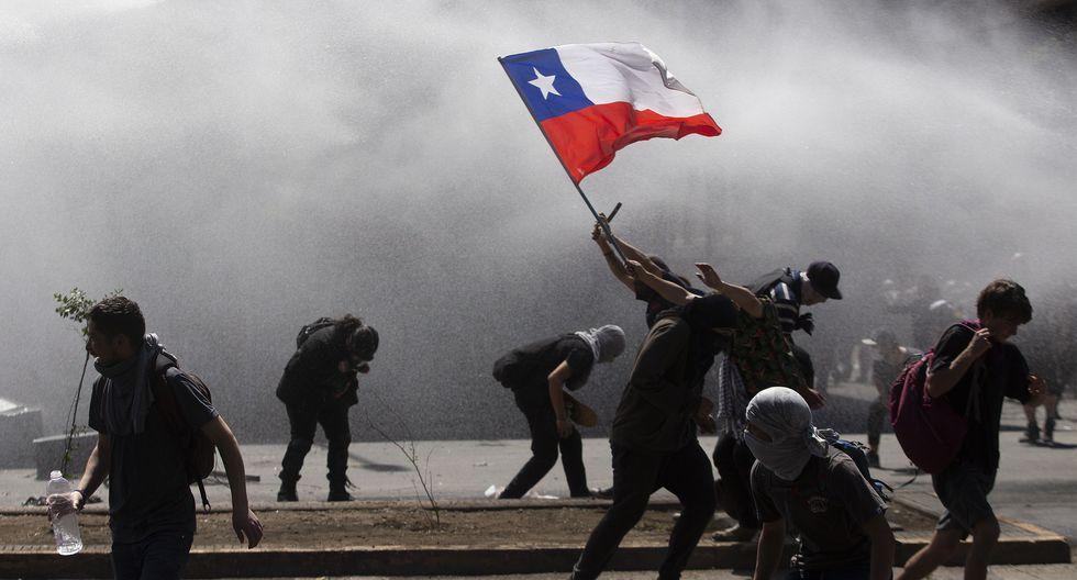 La policía usa su carro lanza agua contra los manifestantes. (Photo by CLAUDIO REYES / AFP).