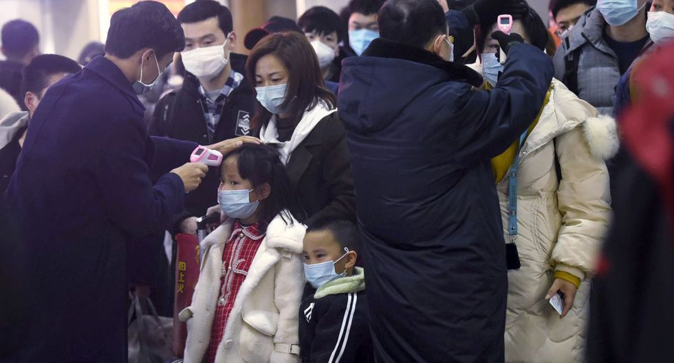 Workers use infrared thermometers to check the temperature of passengers arriving from Wuhan at a train station in Hangzhou in eastern China's Zhejiang Province, Thursday, Jan. 23, 2020. China closed off a city of more than 11 million people Thursday in an unprecedented effort to try to contain a deadly new viral illness that has sickened hundreds and spread to other cities and countries in the Lunar New Year travel rush. (Chinatopix via AP)
