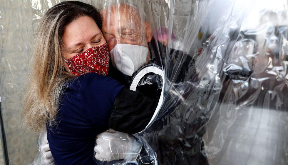 """María Paula Moraes se encuentra con su padre Wanderley de 82 años, que vive en una residencia de ancianos en la ciudad de Sao Paulo (Brasil),. La """"cortina de abrazos"""" sirve como una alternativa válida para amenizar las medidas de distanciamiento social en medio del coronavirus. (EFE/Sebastião Moreira)."""