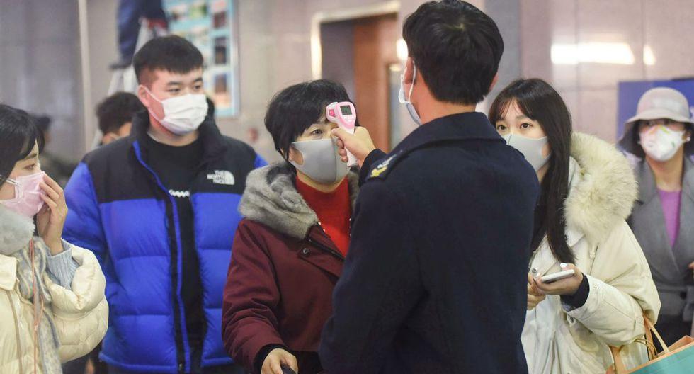 Un trabajador verifica la temperatura corporal de un pasajero después de que un tren de Wuhan llegara a la estación de tren de Hangzhou, en la provincia oriental china de Zhejiang. (AFP).