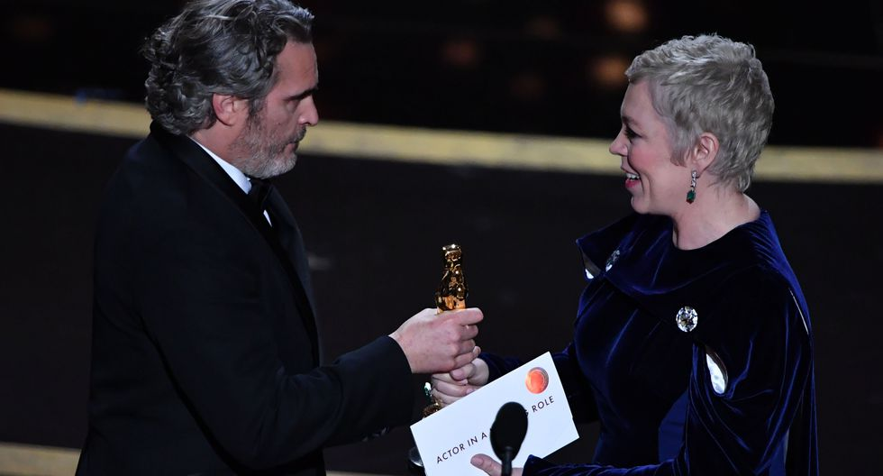 """US actor Joaquin Phoenix (L) accepts the award for Best Actor for """"Joker"""" from British actress Olivia Colman during the 92nd Oscars at the Dolby Theatre in Hollywood, California on February 9, 2020. / AFP / Mark RALSTON"""