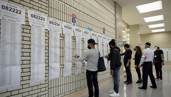 Ciudadanos peruanos residentes en Japón buscan sus nombres en listas electorales en una mesa de votación en Tokio, el 6 de junio de 2021. (EFE/EPA/FRANCK ROBICHON).