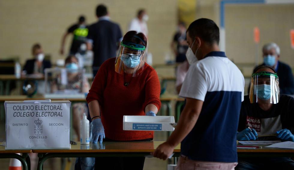 Un hombre que lleva una máscara facial deja su tarjeta de identidad en una bandeja antes de emitir su voto en un colegio electoral en Burela, en el norte de España, durante las elecciones regionales. (AFP/MIGUEL RIOPA).