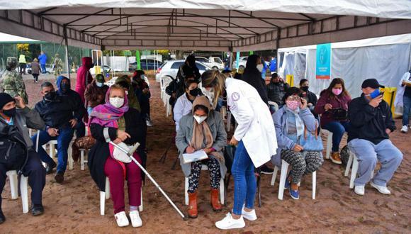 Las personas se sientan mientras esperan para firmar un documento antes de recibir una dosis de una vacuna contra COVID-19 en un centro de vacunación en Villa Elisa, Paraguay. (Foto: AFP / NORBERTO DUARTE).
