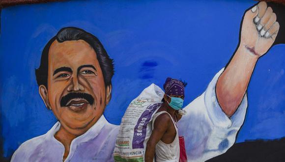 Un indigente que usa mascarilla pasa frente a un mural que representa al presidente de Nicaragua, Daniel Ortega, en Managua el 9 de abril de 2020. (Foto de INTI OCON / AFP).