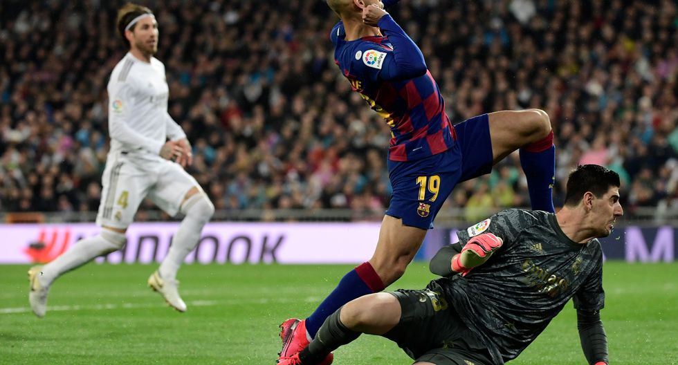 Barcelona´s Danish forward Martin Braithwaite vies with Real Madrid's Belgian goalkeeper Thibaut Courtois (BOTTOM) during the Spanish League football match between Real Madrid and Barcelona at the Santiago Bernabeu stadium in Madrid on March 1, 2020. / AFP / JAVIER SORIANO