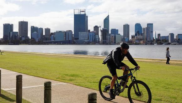 Un hombre monta una bicicleta a lo largo de la playa en Perth el 29 de junio de 2021. Los casos positivos de coronavirus Covid-19 han llevado a un cierre de cuatro días del área metropolitana de Perth, Australia. (Foto de TREVOR COLLENS / AFP).