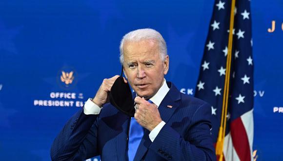El presidente electo de Estados Unidos, Joe Biden, se quita la mascarilla mientras anuncia su equipo económico en el Queen Theatre en Wilmington, Delaware. (Foto de Chandan KHANNA / AFP).