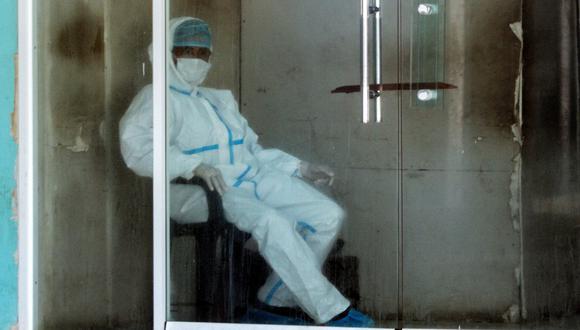 Un hombre con equipo de protección personal (EPP) descansa en la entrada de la sala de emergencias de un hospital de Venezuela, el 2 de julio de 2020, en medio de la pandemia del coronavirus. (Luis BRAVO / AFP).