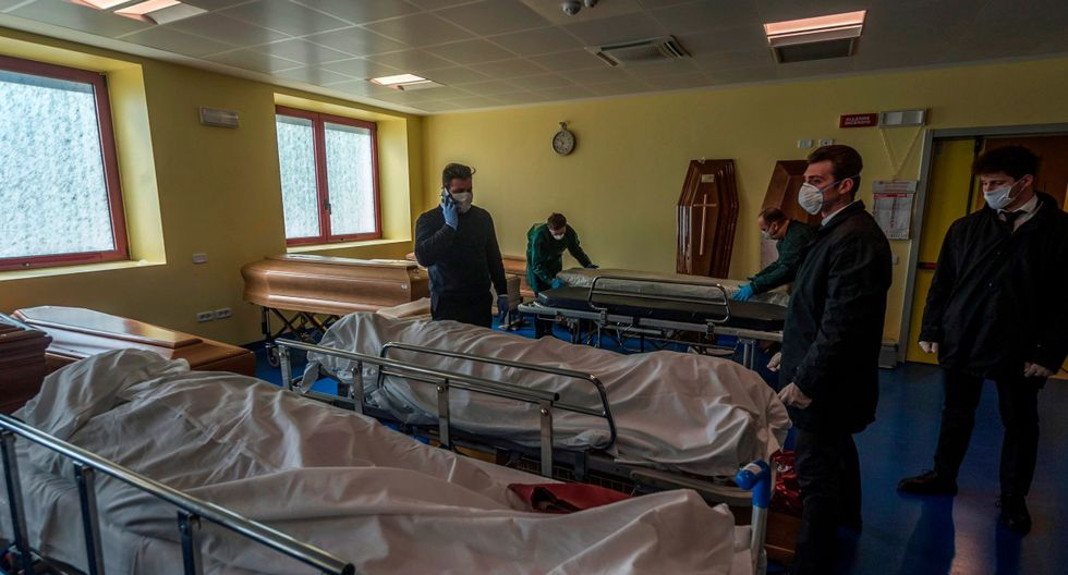 Los trabajadores se paran junto a los ataúdes y los restos de las víctimas del coronavirus, en Bérgamo. (EFE).