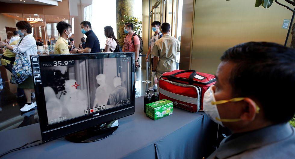 Un trabajador monitorea la pantalla del escáner térmico que muestra la temperatura de los compradores en un centro comercial en Bangkok. (Foto: EFE)