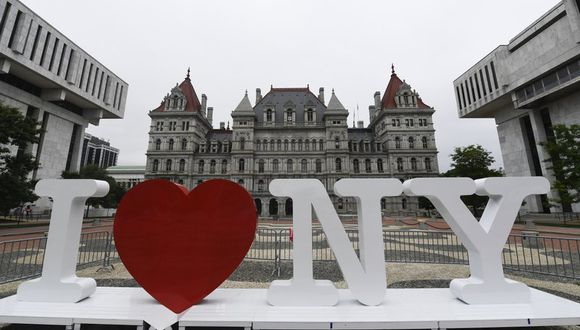 """En esta imagen de archivo, tomada el 18 de junio de 2019, un nuevo cartel promocional con la frase """"I Love NY"""", en la Plaza Empire State, antes de ser instalado ante el capitolio estatal de Nueva York en Albany. Milton Glaser, el creador del logo, falleció el 26 de junio de 2020 en su 91er cumpleaños. (AP Foto/Hans Pennink, archivo)."""