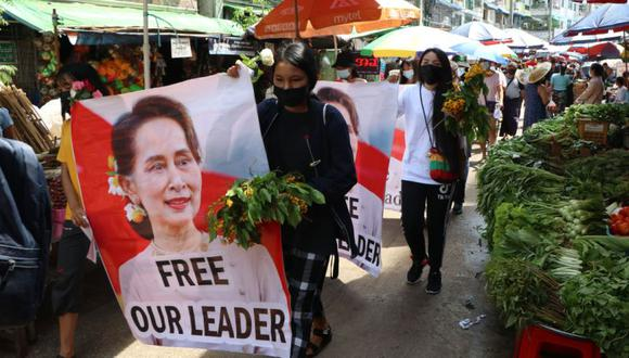 Los manifestantes antigolpistas caminan por un mercado con imágenes de la derrocadoalíder birmano Aung San Suu Kyi en el municipio de Kamayut en Yangon, Myanmar. (Foto: AP)