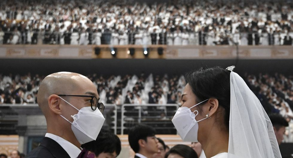 Una pareja con máscaras protectoras asiste a una ceremonia de boda masiva organizada en Corea del Sur, pese a riesgos de contaminación y los más de 20 casos de infección del coronavirus en el país. (Foto: AFP)