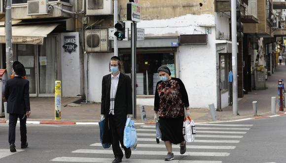 Unas personas pasean con mascarillas por la ciudad israelí de Bnei Brak, cerca de Tel Aviv, el pasado mes de abril. (Foto: Menahem Kahana/AFP).