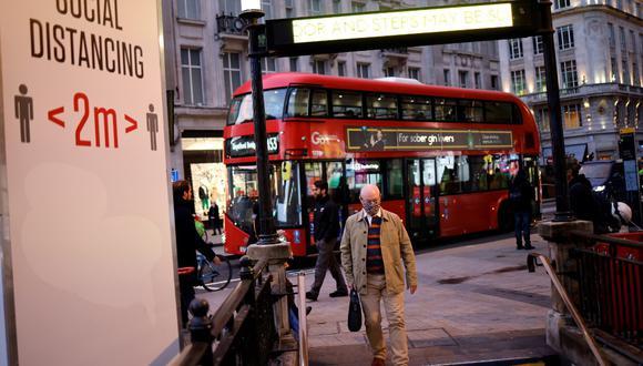 Un hombre utiliza una cubierta facial como medida de precaución contra el COVID-19, camina hacia la estación de metro de Oxford Circus, en el centro de Londres. (Tolga Akmen / AFP)