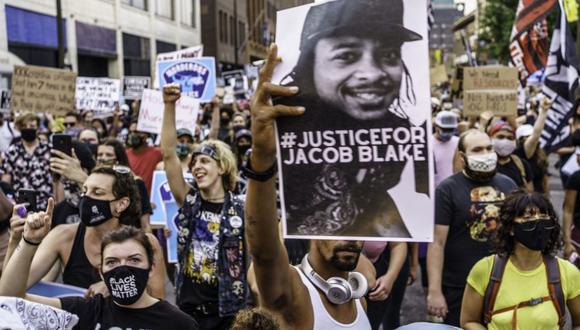 Los manifestantes marchan cerca de la primera comisaría de policía de Minneapolis durante una manifestación contra la brutalidad policial y el racismo para exigir justicia para Jacob Blake. (Foto de Kerem Yucel / AFP).