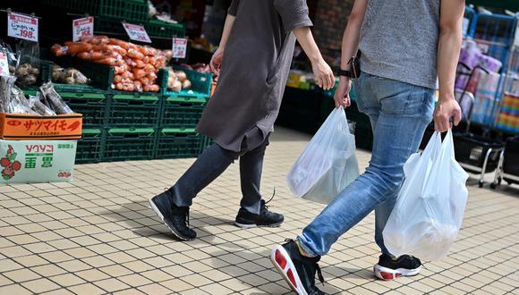 En esta foto, tomada el 24 de junio, se aprecia a un cliente llevando sus compras en bolsas de plástico cuando sale de un supermercado en Tokio. (CHARLY TRIBALLEAU / AFP)
