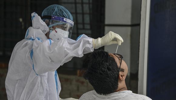 Un personal médico realiza un hisopado a una persona en la India. (Foto: Diptendu DUTTA / AFP)