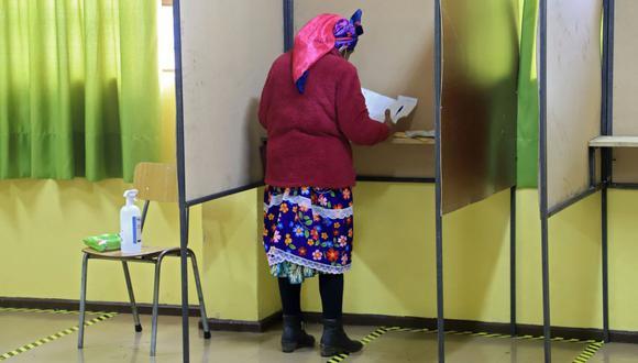 Una mujer indígena mapuche vota durante las elecciones para elegir alcaldes, concejales y una comisión para reescribir la Constitución en Temuco, Chile. (Foto de MARIO QUILODRAN / AFP).