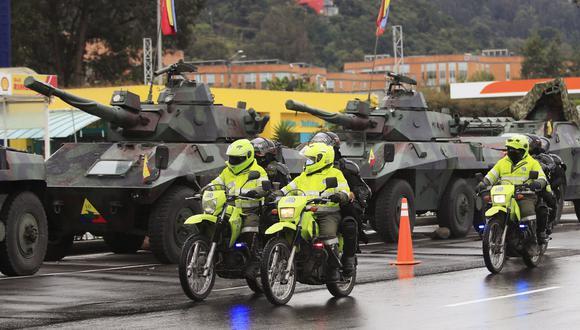 Policías antidisturbios pasan frente a tanques del Ejército en las afueras de Bogotá, Colombia, el 4 de mayo de 2021. (Foto de DANIEL MUNOZ / AFP).