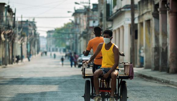 Hombres con mascarillas viajan en un rickshaw por una calle de La Habana. (Foto: Archivo / YAMIL LAGE / AFP).